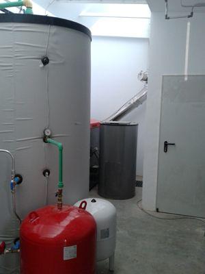 Local de instalaciones con acumulador solar, caldera de biomasa al fondo y silo de obra a la derecha